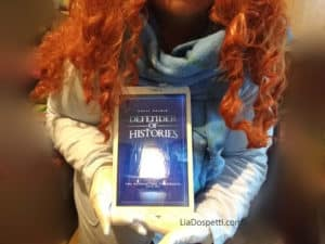 Lia Dospetting holding her tablet with the book cover - Defender of Histories Book Review